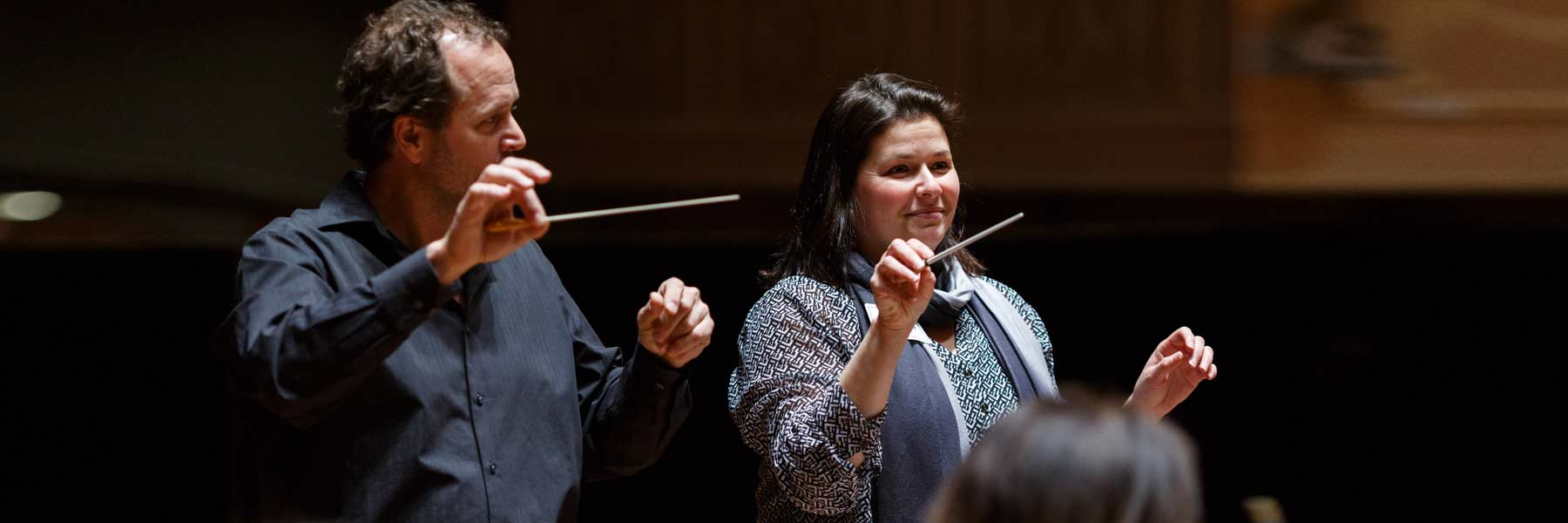 A man and woman practice conducting an orchestra.